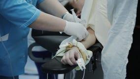 Inserzioni di medico in una vena nel paziente che anestetizza nella sala operatoria archivi video