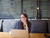 Inserzionista femminile allegro che ha conversazione telefonica delle cellule, sedentesi in caffè con il NET-libro Fotografia Stock