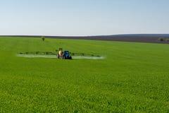 Inseticida de pulverização do trator em um campo de trigo imagens de stock royalty free
