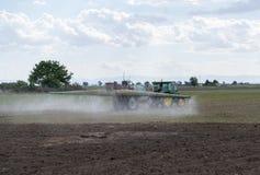 Inseticidas de pulverização do trator no campo com pulverizador O fazendeiro fertiliza plantas fotos de stock