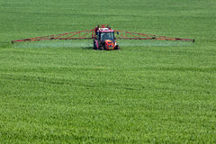 Inseticidas de pulverização do trator no campo verde grande imagens de stock royalty free