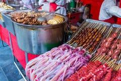 Insetos Roasted e crus, bichos-da-seda, escorpião, erros, serpentes, carne de cão, polvo na vara fotografia de stock