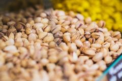 Inshell pistachios on the counter of the grocery market. Harvest nutritious nuts in the store. Vegetarian healthy diet. Ingredients for salads, appetizers and royalty free stock photos