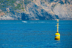 Inshore yellow buoy floating in the deep blue sea. Warning concept, reporting Stock Images