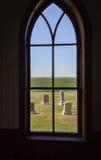 Insida som ser ut ur det välvda kyrkliga fönstret som ser den allvarliga gården Arkivfoto