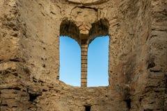 Insidan av forntida stentegelsten fördärvar byggnad med det välvda fönstret och blå himmel arkivbild