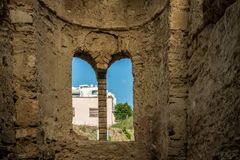 Insidan av forntida stentegelsten fördärvar byggnad med det välvda fönstret och blå himmel och byggnader utanför royaltyfri fotografi
