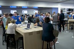 Inside The Apple Store - Fifth Avenue, NYC. Open 24 hours a day, The Fifth Avenue Apple Store in New York City never sleeps. Customers line up for assistance Royalty Free Stock Photo