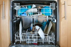Inside of as dishwasher containing dirty dishes Royalty Free Stock Photography