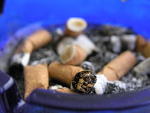 Inside an ashtray. An ashtray with an overflow of cigarettes after a stressful meeting Royalty Free Stock Images