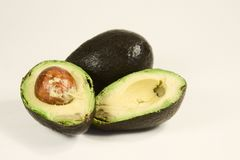 Inside Avacado. Hass Avacado's one sliced in half and one whole isolated on white Stock Photo