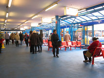 Inside Bedford bus station. People waiting for buses in the bus station at Bedford, united kingdom. Buses can be seen outside the windows. There are plans to Royalty Free Stock Image
