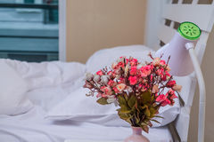 Inside the bedroom are white and flower vases on the bedside table. Stock Images