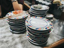 Inside a belt sushi restaurant. Consumers pile up colored empty plates when they are finished eating royalty free stock images