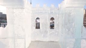 Inside big ice castle in town with road at sunny winter day stock footage