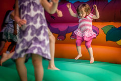Inside bouncy castle. Cute little girl jumping inside the inflatable bouncy castle royalty free stock images