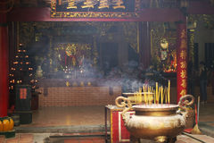 Inside Buddhist Temple. The interior of a Buddhist temple in Vietnam. In the foreground, a ceremonial urn is filled with sticks of burning incense that are royalty free stock image