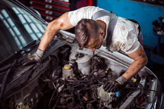 Inside of car bonnet. Male mechanic is checking parts of car bonnet Stock Photo