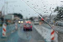 Inside car when rainning, Road view wtih restriction signs through car window with rain drops. Drizzle on the windshield. Drizzle on the windshield, Inside car royalty free stock photo