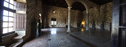 Inside Castle. Big room with fire place, mosaics, columns and arcs inside medieval castle Stock Photo