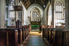 Inside the church at Selworthy in Somerset. Looking down the nave of the medieval Church of all Saints at Selworthy in Somerset, showing the altar, pews, stained stock photography
