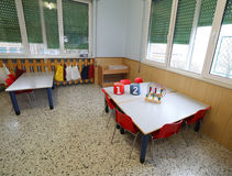 Inside of a classroom with chairs and benches and some toys on t. Inside of a classroom with small red chairs and benches and some toys on the tables royalty free stock photos
