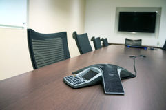 Inside A Conference Room. A typical conference or meeting room complete with telephone, whiteboard, television for teleconferencing and calls stock photography