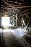 Inside a Connecticut Covered Bridge. Light filters into an old covered bridge along highway 7 in Connecticutt Stock Images