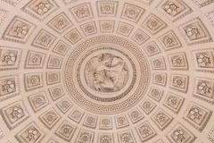 Inside of a cupola, ornate ceiling with a dome. The inside of a dome ceiling, ornate with coffers containing floral ornaments, a meander border and a kneeling royalty free stock images