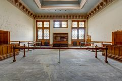 Old Fashioned Courtroom with Large Windows - Abandoned Courthouse. Inside a derelict courtroom with with a skylight and large floor to ceiling windows at an Stock Image