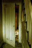 Inside Doorway of Abandoned House. A doorway inside an abandoned house is slightly open Royalty Free Stock Image