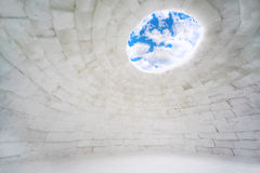 Inside empty house of ice. Eskimo igloo, blue sky and clouds Stock Images