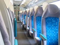 Inside an empty modern train carriage. The inside of a modern and new train carriage, There are no passengers it is empty. Blue new seats Stock Image