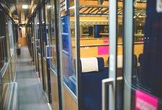 Inside an empty passenger car high-speed train. In the evening Stock Photos
