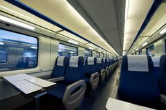 Inside of an empty passenger train car. Empty interior of a passenger train car (aka coach or carriage). Rows of unoccupied seats and folding tables in economy Royalty Free Stock Images