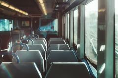 Inside of an empty suburban train. An interior of a modern empty ordinary suburban train in Europe with a row of double seats, shallow depth of field with royalty free stock photography
