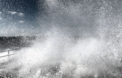 Exploding water wave. Inside an exploding wave of ocean water as it breaks over a coastal defense wall in Tywyn, Wales royalty free stock photos