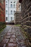 Narrow street in the fortress. Inside the fortress a small short street is paved with cobblestone. On the left and right are stone buildings. Vyborg, Russia Royalty Free Stock Photos