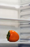 Inside Fridge. A persimmon inside fridge, sitting alone on the shelf. Copyspace provided Stock Images