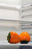 Inside Fridge. Two persimmons inside fridge, sitting alone on the shelf. Copyspace provided Stock Photos