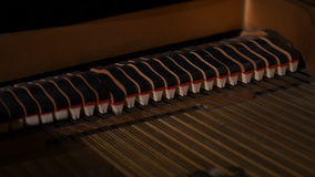 Inside grand vintage piano strings and keys. Piano hammers playing keys closeup. Inside grand vintage piano strings and keys stock footage