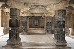 Inside Hindu Temple, Hampi, India. Inside Hindu Temple in the archaeological complex of the ruins of Hampi, India. Hall with black columns with bas-reliefs stock image