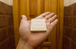 Inside the hotel room, one hand of a visitor holding small piece of bathe soap frjm toiletries in a guest house bathroom Stock Images