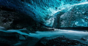 Inside ice cave with flowing river stock video footage