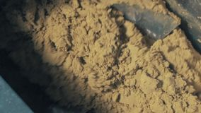 Inside of industrial machinery metal blades mincing yellow kinetic sand mass stock video footage