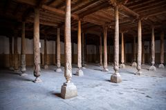 Inside Juma Friday Mosque in Khiva. Khorezm Region, Uzbekistan. Huge ancient wooden columns with carvings and mysterious light stock image