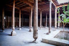 Inside Juma Friday Mosque in Khiva. Khorezm Region, Uzbekistan. Huge ancient wooden columns with carvings and mysterious light royalty free stock photos