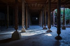 Inside Juma Friday Mosque in Khiva. Khorezm Region, Uzbekistan. Huge ancient wooden columns with carvings and mysterious light stock images