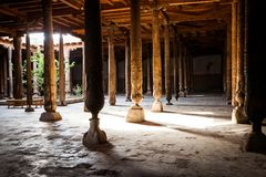 Inside Juma Friday Mosque in Khiva. Khorezm Region, Uzbekistan. Huge ancient wooden columns with carvings and mysterious light stock photo