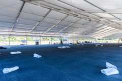 Inside large white tent for entertaining in field. Inside of a large white tent in a grass field for parties and enteraining Royalty Free Stock Photo